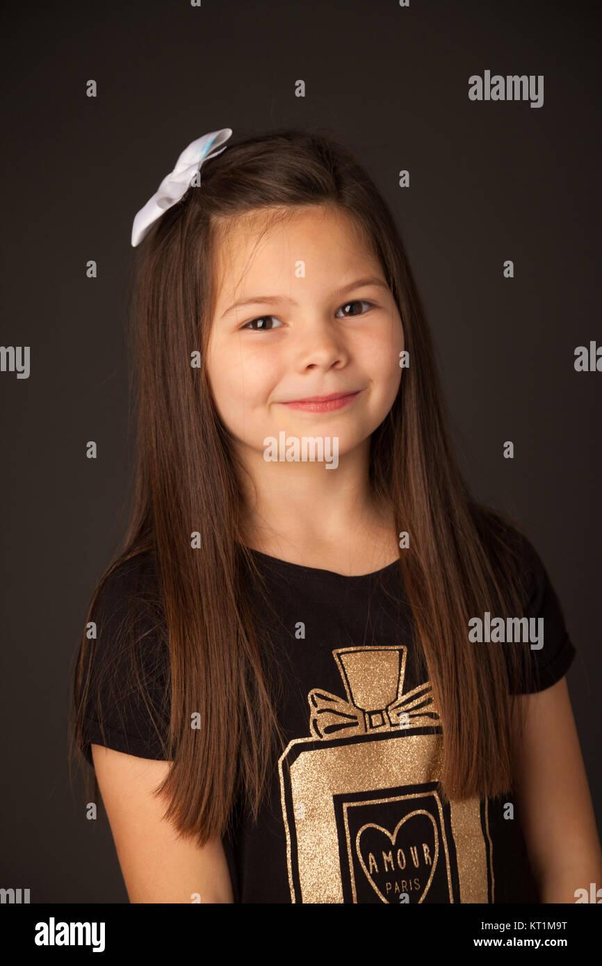Retrato de una niña de siete años de pie frente a un fondo oscuro. Imagen De Stock