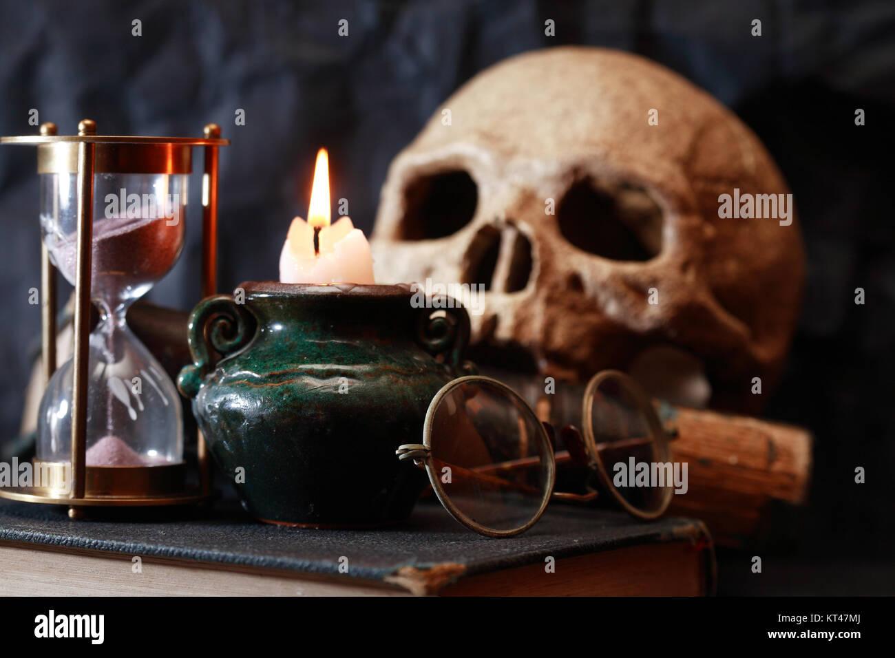 Vintage bodegón con iluminación de velas y el cráneo, cerca del reloj de arena Foto de stock