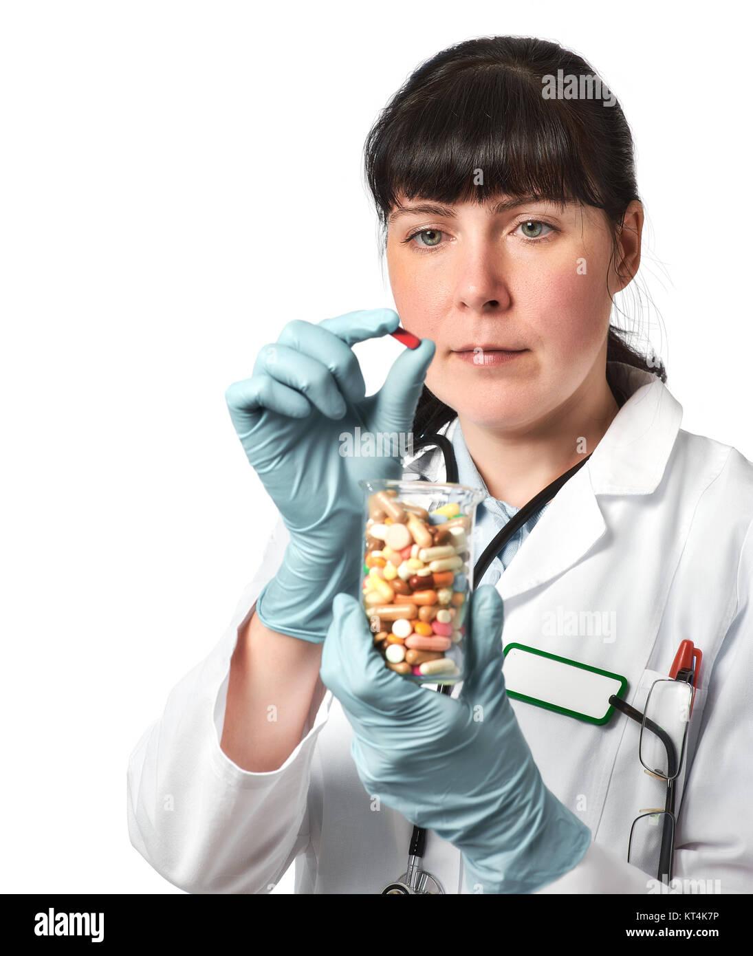 Doctora o enfermera con vidrio lleno de píldoras en mano enguantada sosteniendo una pastilla roja en pinzas. DOF Foto de stock