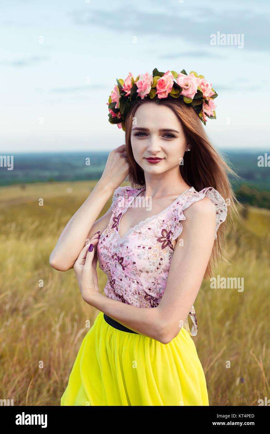 752425b88 Hermosa Hermosa niña bonita moda en vestidos en el campo de flores. Linda  chica con corona de flores en la cabeza y ramo de muchas flores amarillas  sentado ...