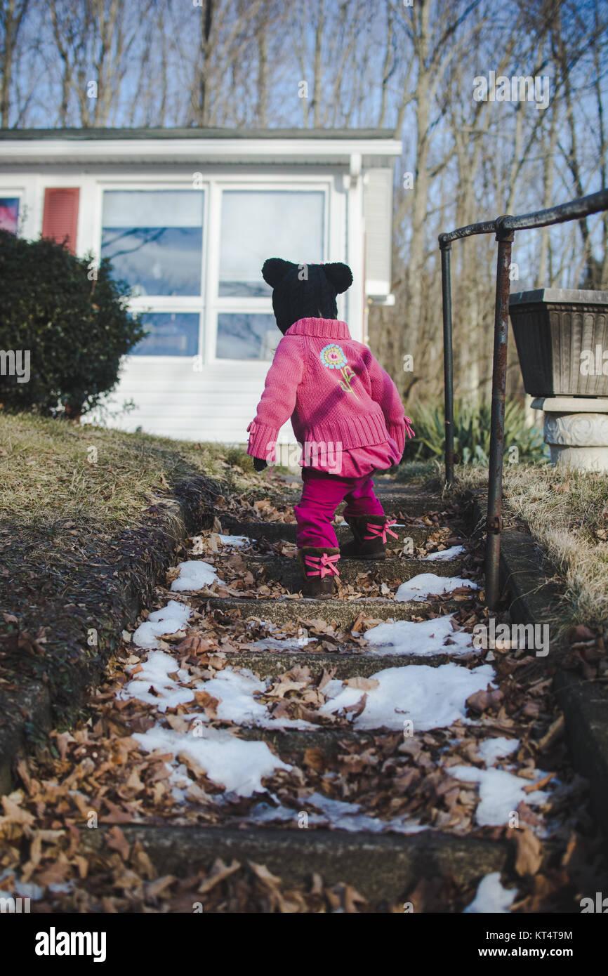 Un niño se sube un tramo de escaleras de piedra vistiendo un suéter durante el invierno Imagen De Stock
