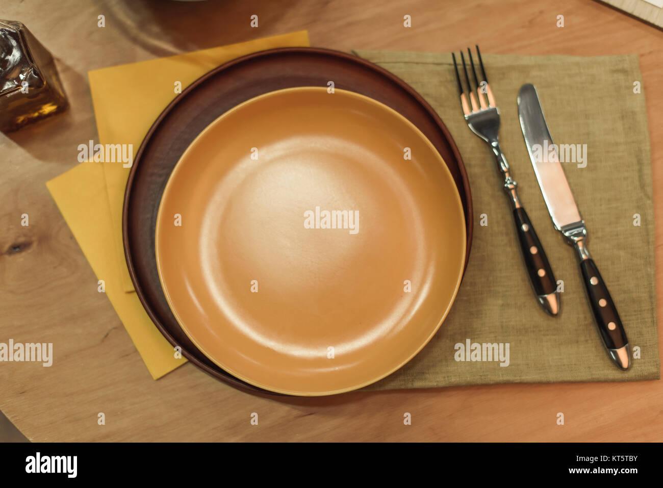 Vista superior del vacío platos, cubiertos y servilletas en superficie de madera Foto de stock