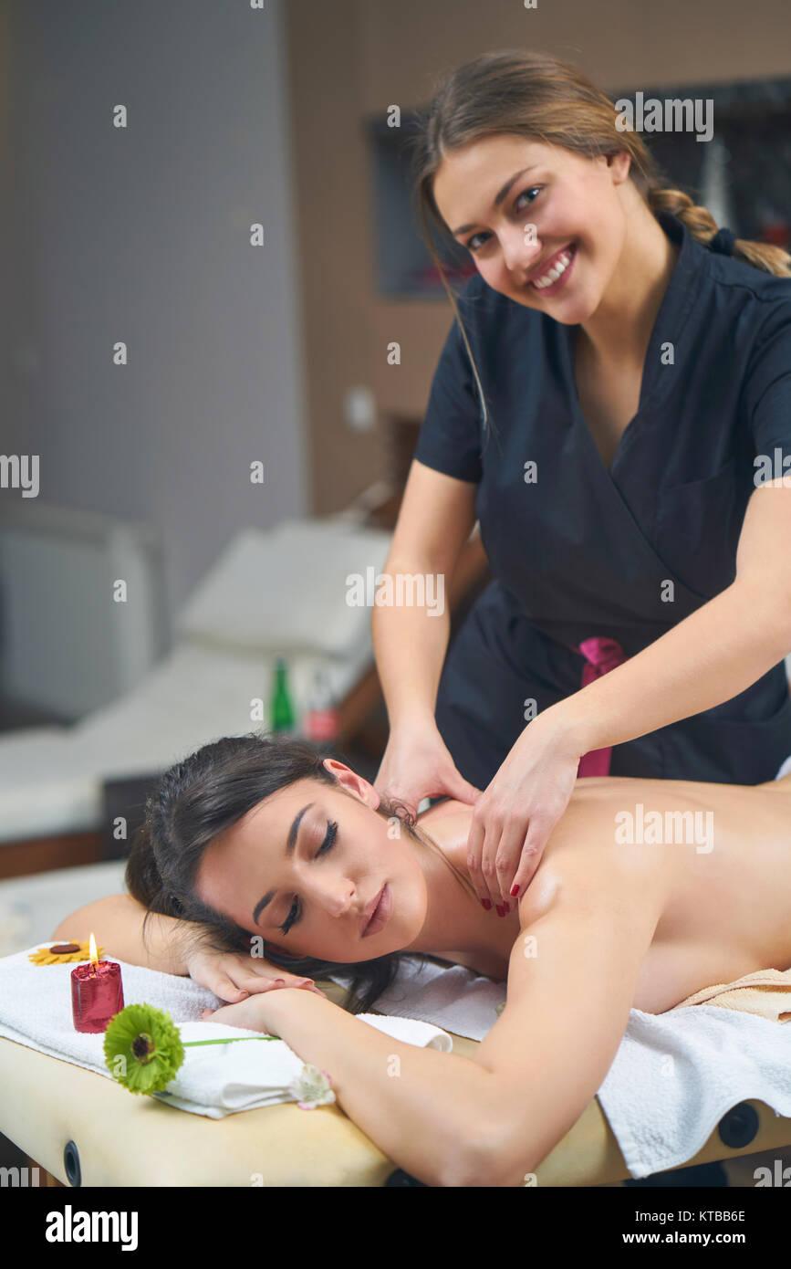 Spa mujer. Mujeres disfrutando relajante masaje de espalda en cosmetología Spa center. El cuidado del cuerpo, Imagen De Stock
