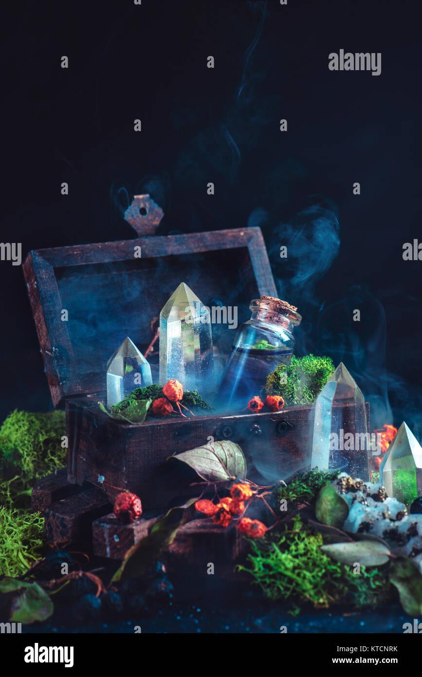 Still life mágico con un arca de madera, botella de poción, cristales, musgo, las bayas y las hojas sobre Imagen De Stock