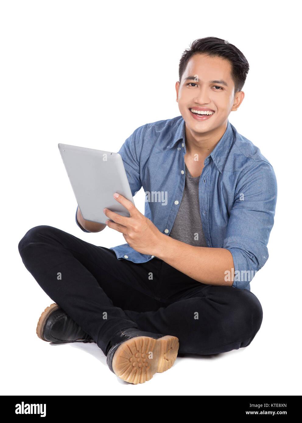 Joven hombre asiático con tablet PC mientras está sentado en el suelo, isol Imagen De Stock