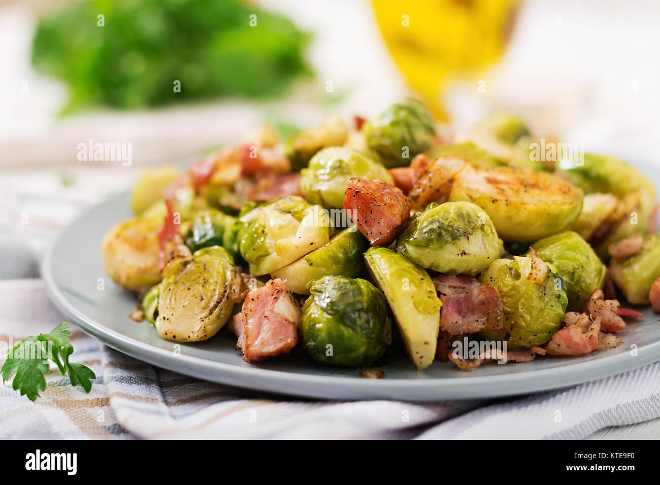 Las coles de Bruselas. Asados de coles de bruselas con bacon. Un delicioso almuerzo. Foto de stock