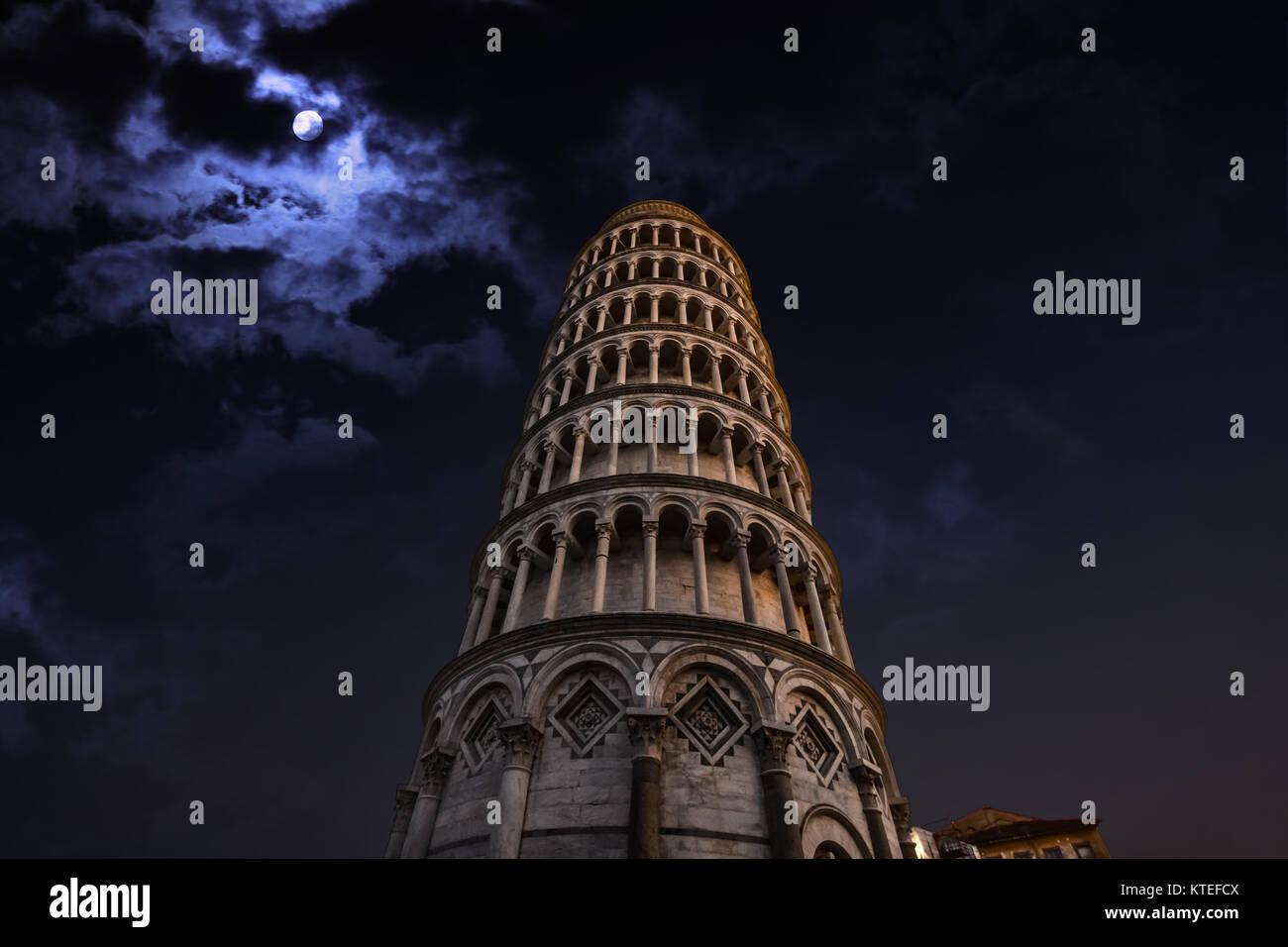La torre inclinada de Pisa, Italia, en la Plaza de los Milagros, iluminado durante la noche con una luna llena detrás Foto de stock