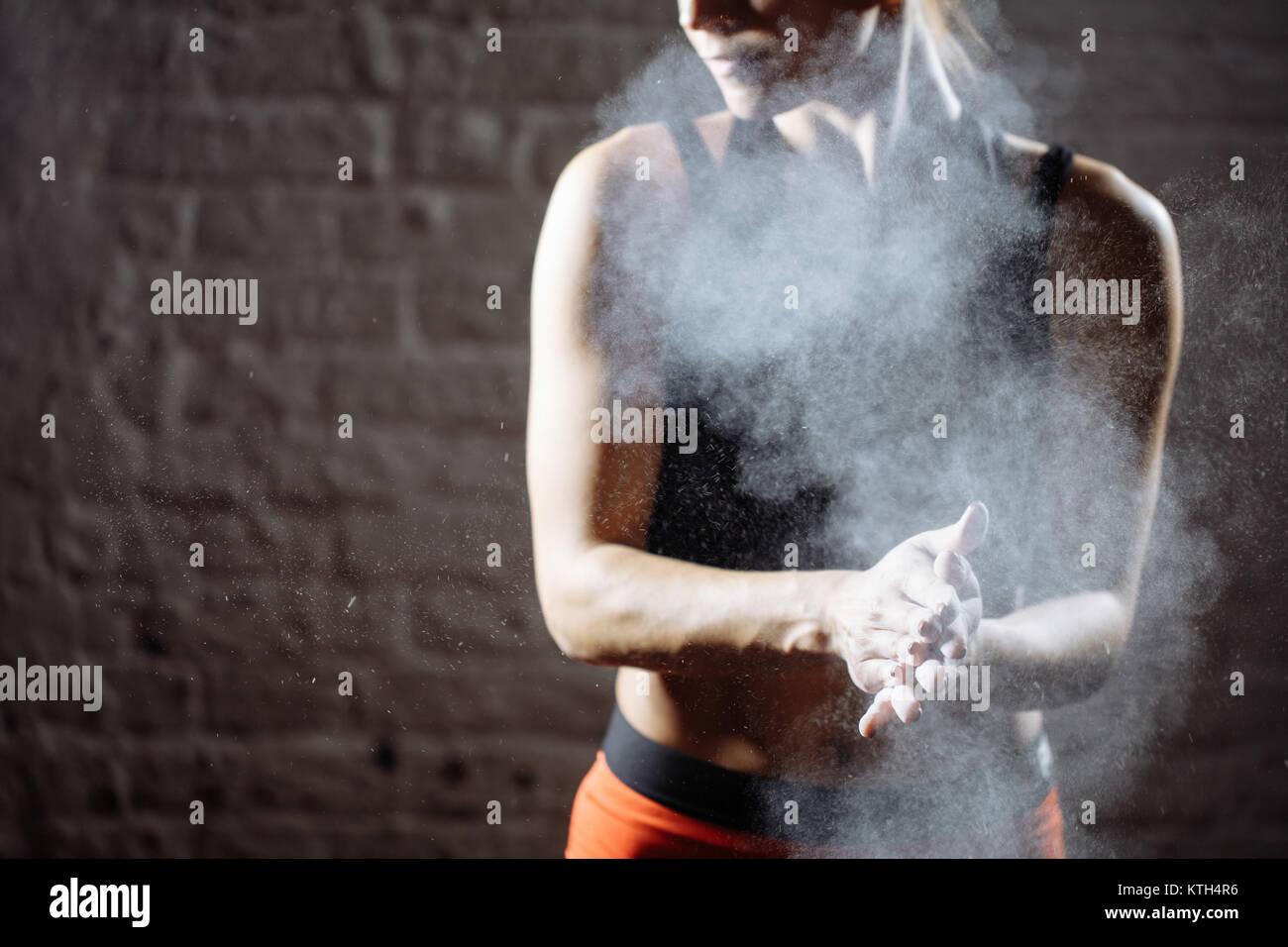 La atleta femenina de las palmas con tiza en polvo antes de que el entrenamiento de fuerza Imagen De Stock