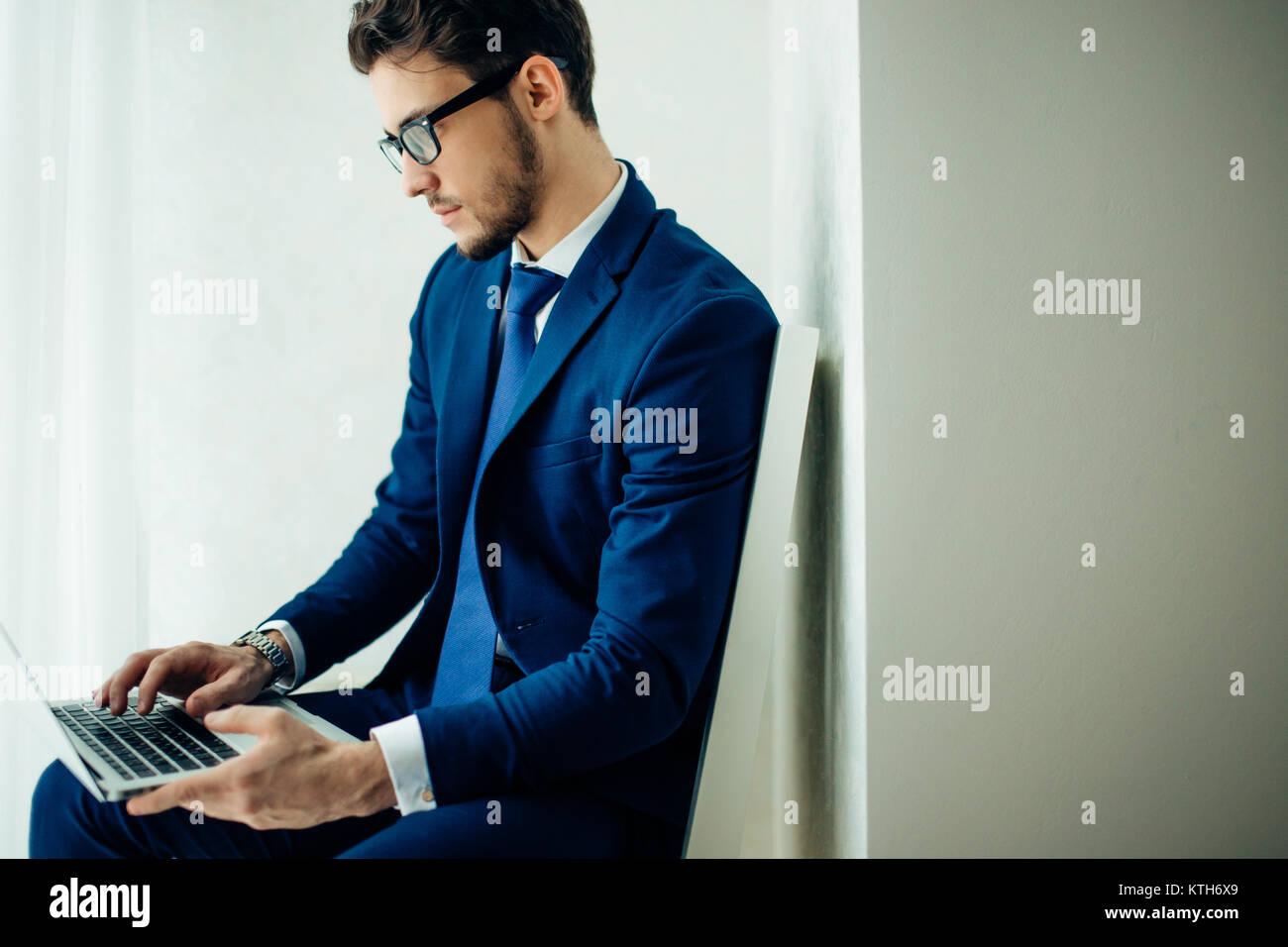 Joven empresario trabajando con un portátil en la oficina Imagen De Stock