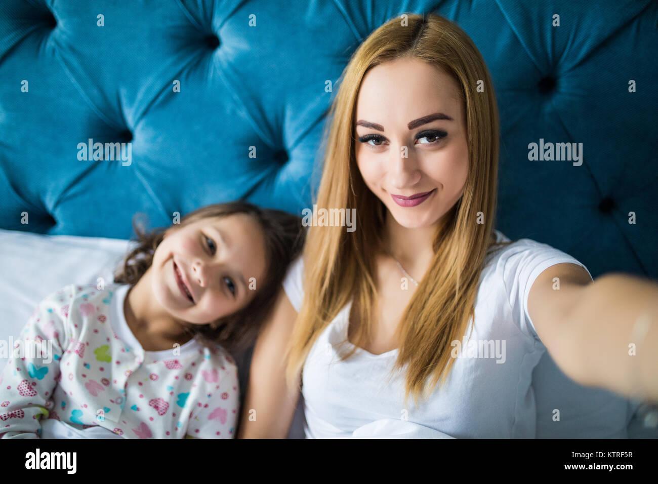 Feliz madre e hija teniendo selfie con el smartphone en la cama Foto de stock