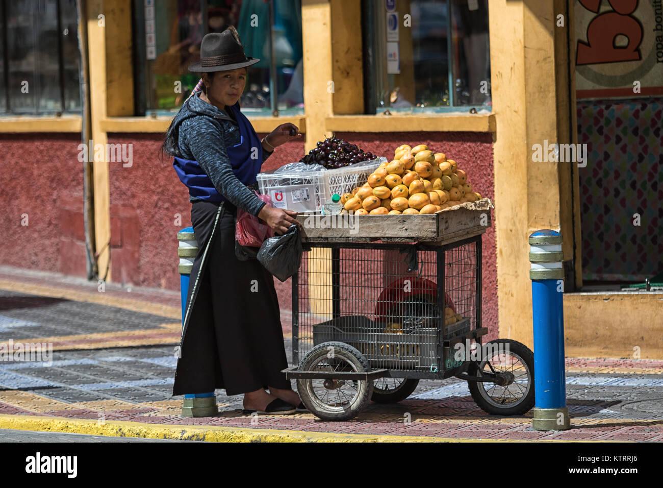 Otavalo, Ecuador-December 23, 2017: la mujer indígena vendiendo frutas om la calle n de la popular ciudad turística Imagen De Stock