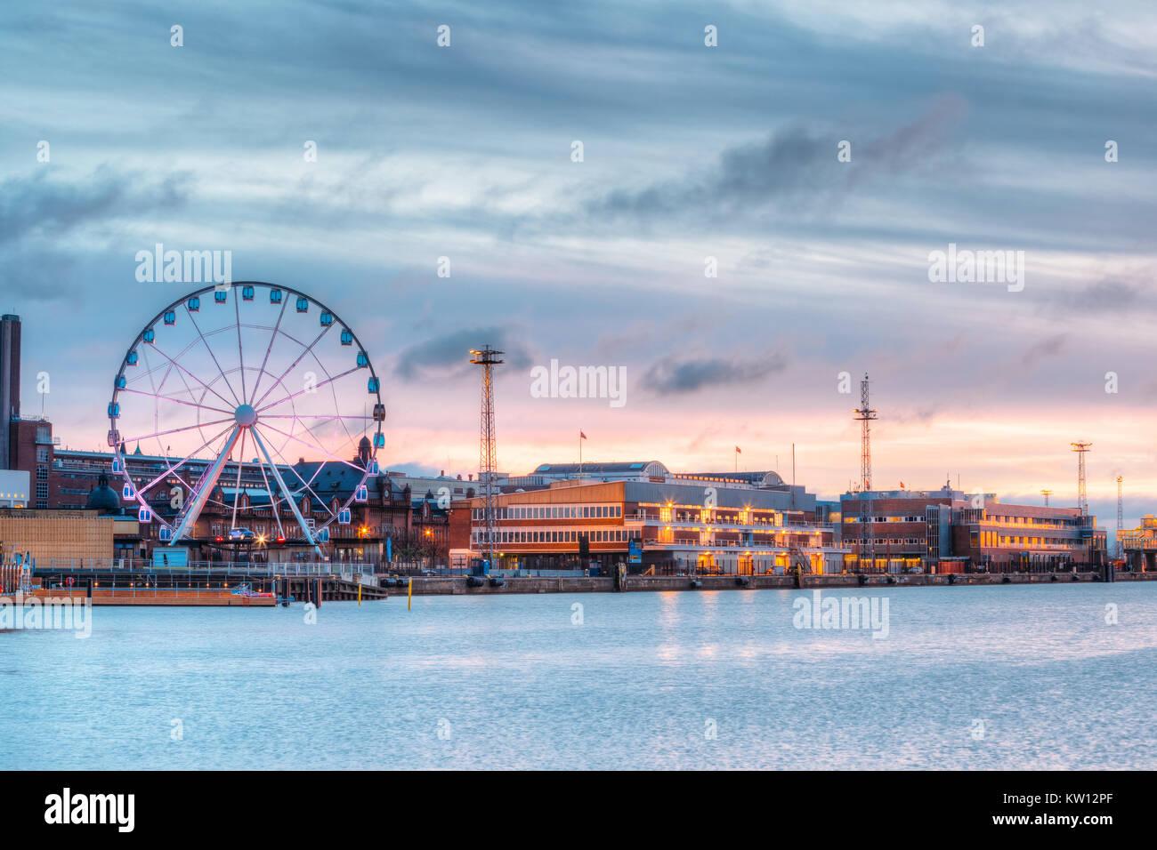 Helsinki, Finlandia. Vista del terraplén con rueda de Ferris en la tarde noche Iluminaciones. Foto de stock