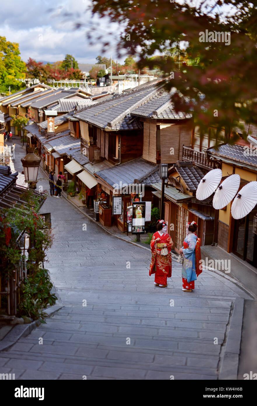 Dos aprendices de geisha, Maiko en coloridos kimonos de pie en una antigua calle Yasaka dori en Kyoto, cerca de Imagen De Stock