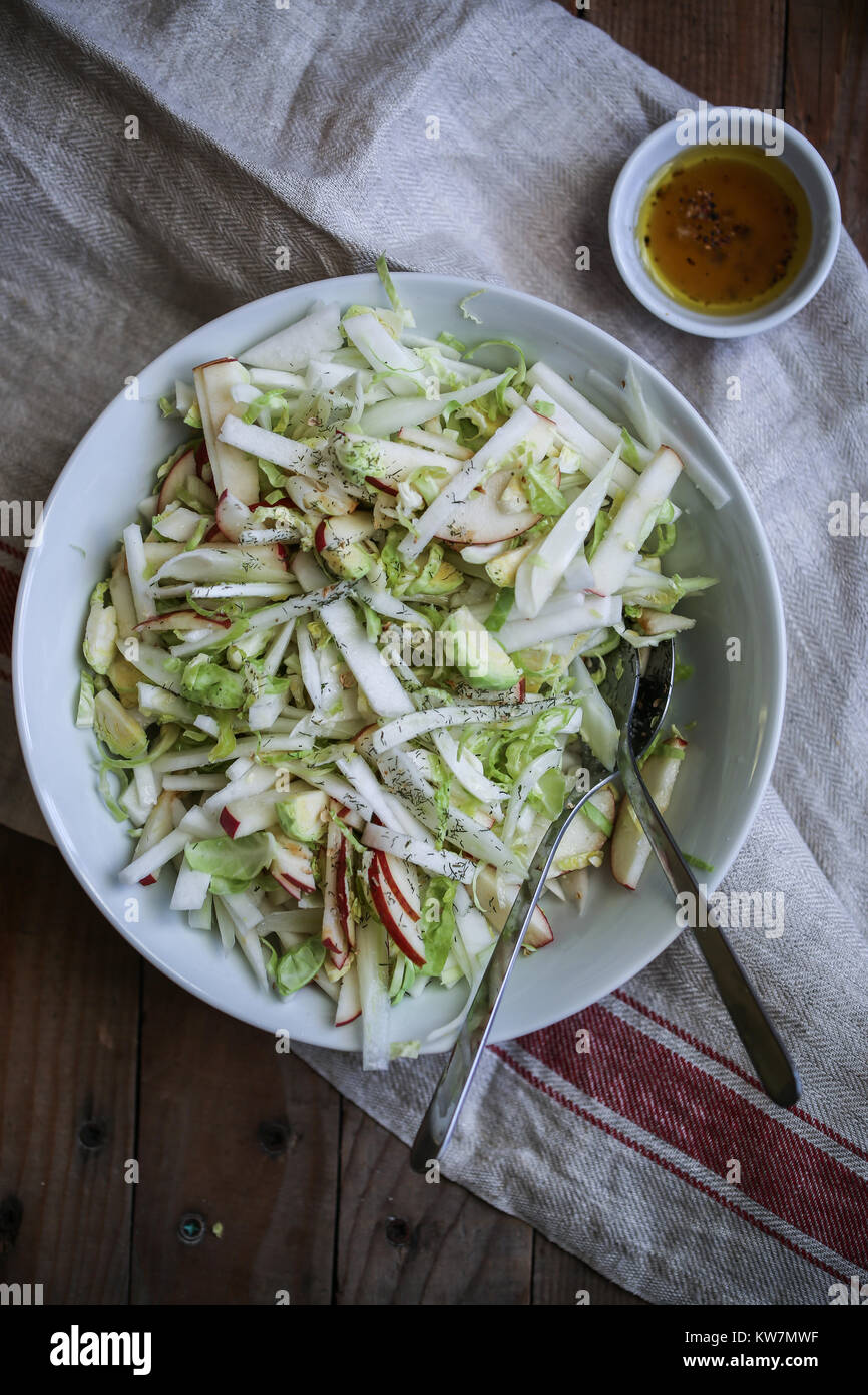 Vegan fresca y saludable ensalada con hinojo, col de bruselas, la manzana, el apio nabo blanco. Citronette con picante Imagen De Stock