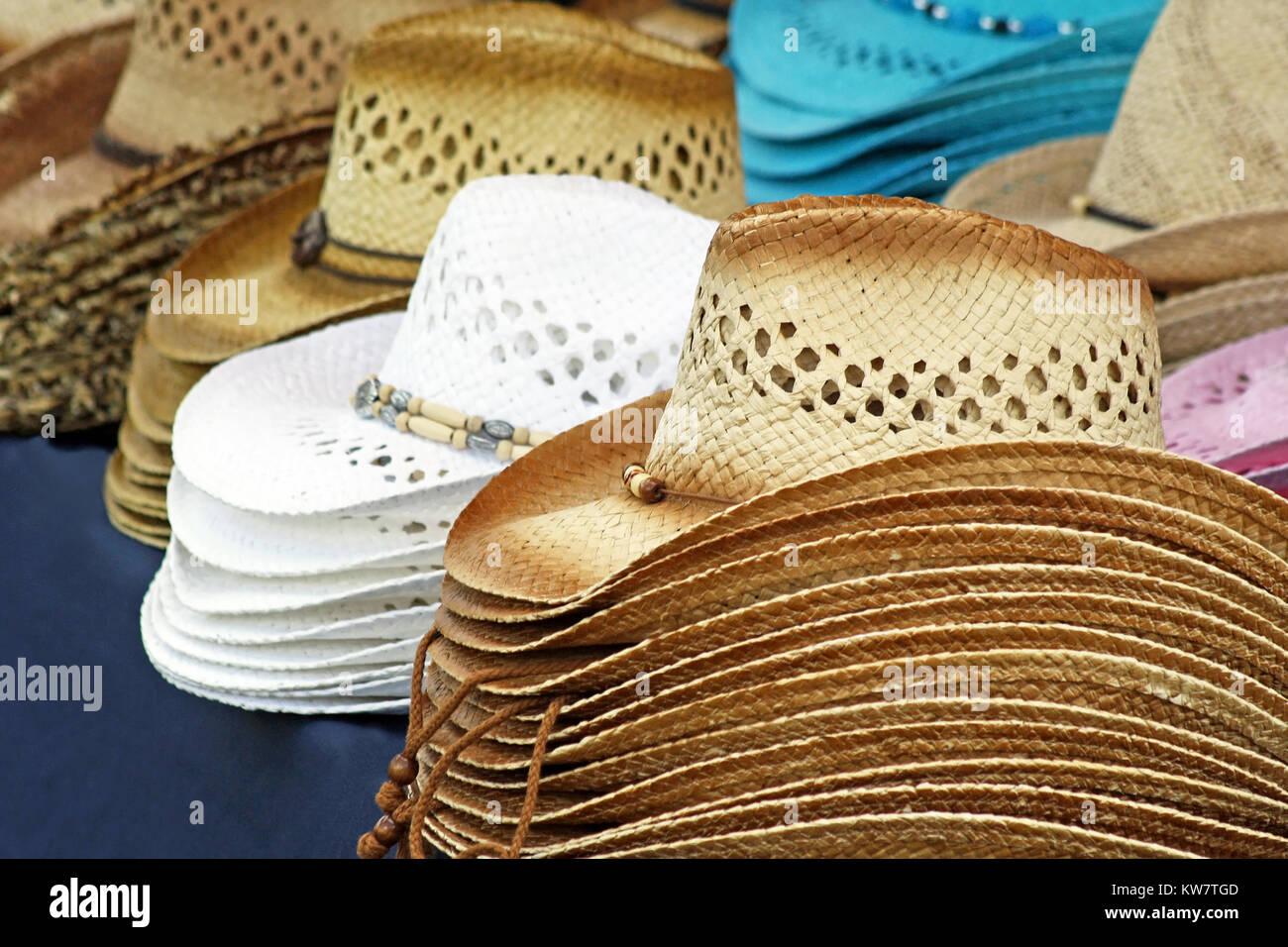 Sombreros de vaqueros de Venta - sombreros de paja de varios colores y diseños  se alinearon en la tabla de Vendedor e6bbfc0492be