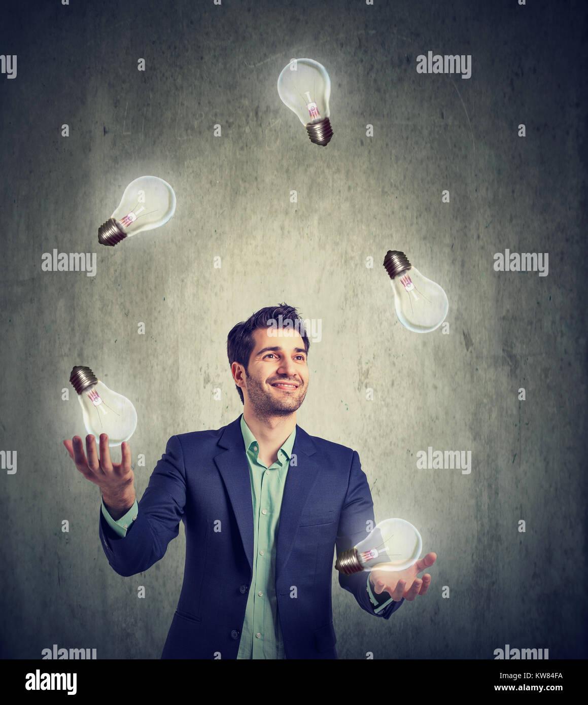 Empresario malabarismo con ardor bombillas teniendo un montón de grandes ideas. Imagen De Stock