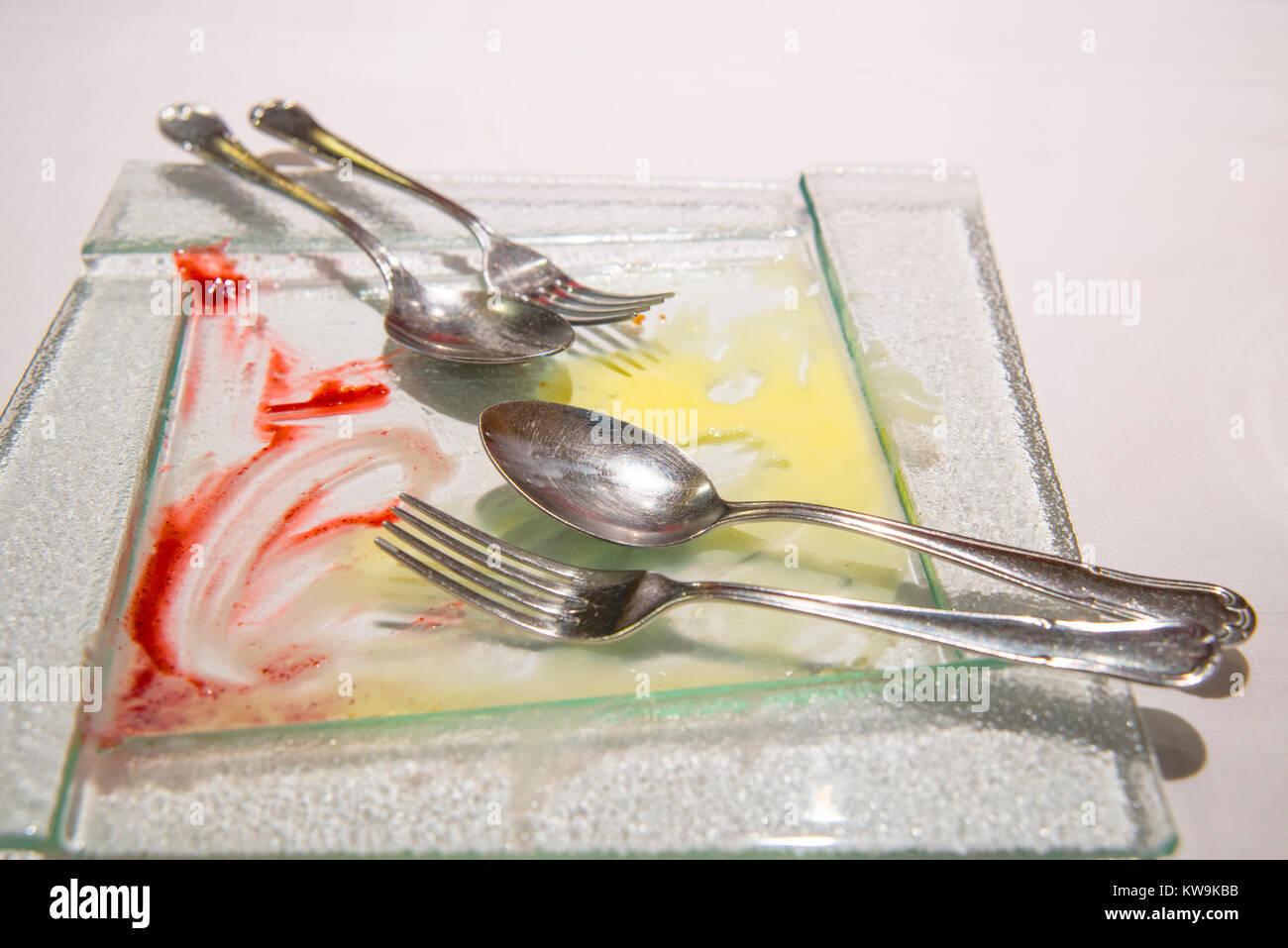 Después de comer postre: plato vacío con horquillas y cucharas. Imagen De Stock