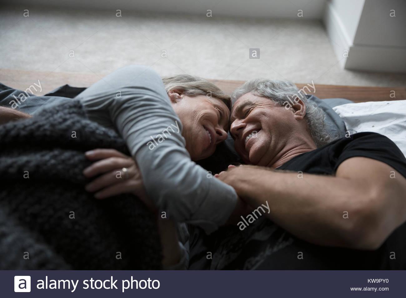 Afectuoso,romántica pareja senior caricias en la cama Imagen De Stock