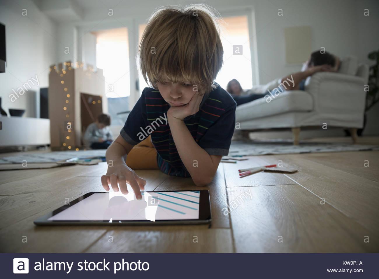 Centrado boy dibujo con tableta digital en el salón piso Foto de stock