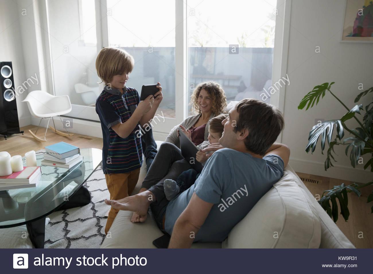 Hijo con teléfono con cámara de fotografiar a la familia en el sofá relajante Imagen De Stock