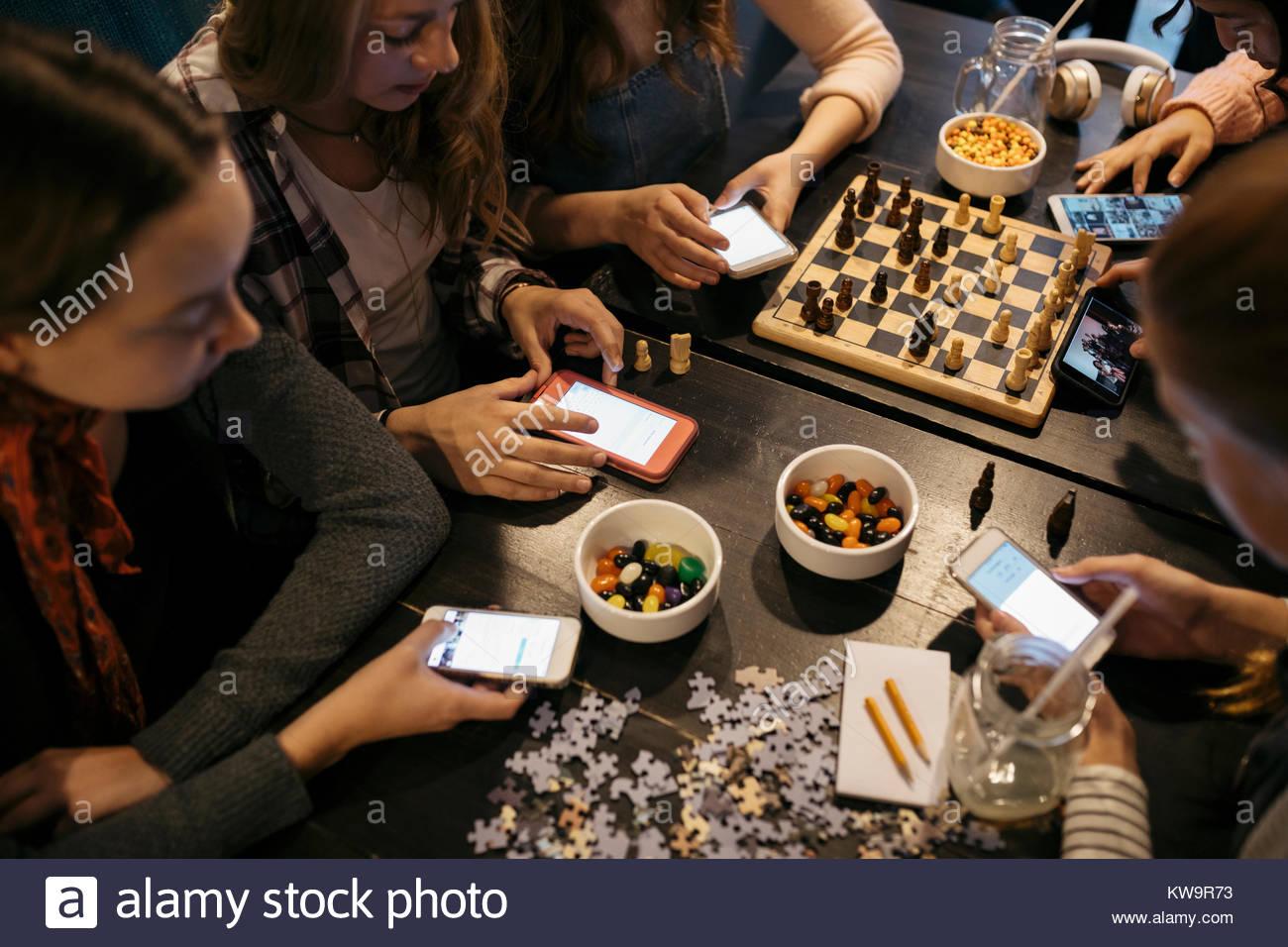 Tween amigas jugando al ajedrez, armar rompecabezas y texto con teléfonos inteligentes en la mesa Imagen De Stock