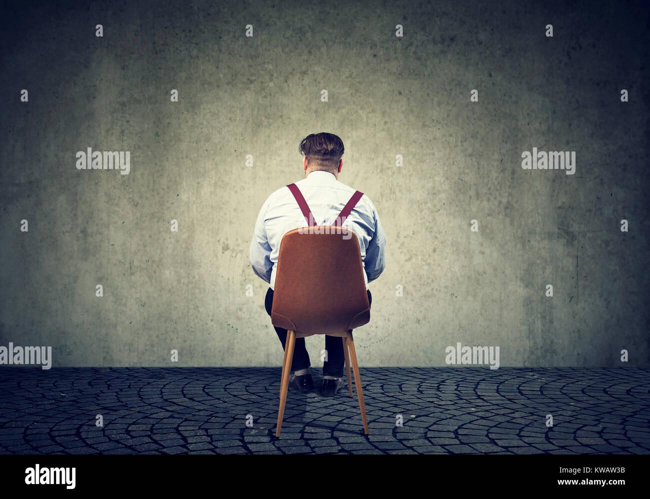 Vista posterior del hombre sentado en una silla mirando la pared gris de hormigón teniendo problemas. Imagen De Stock