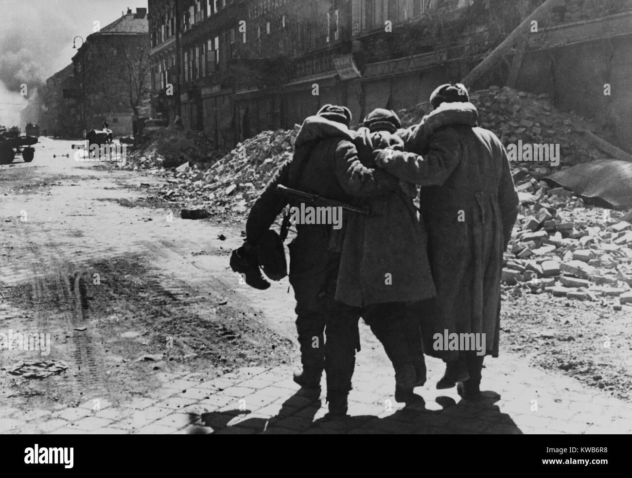 Heridos (Ruso) soldado soviético ayudado por dos compañeros en una calle llena de escombros, de Viena. 1945 Guerra Foto de stock