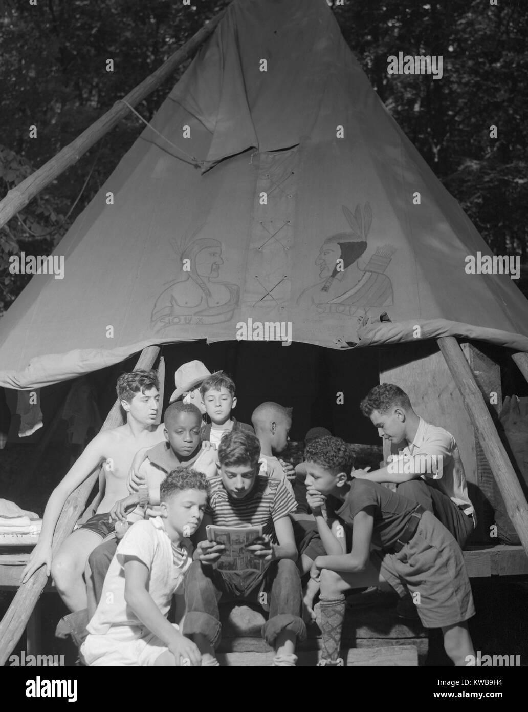 Grupo racialmente integrado de chicos compartiendo un libro de historietas en el campamento de Nathan Hale en Southfields, Foto de stock