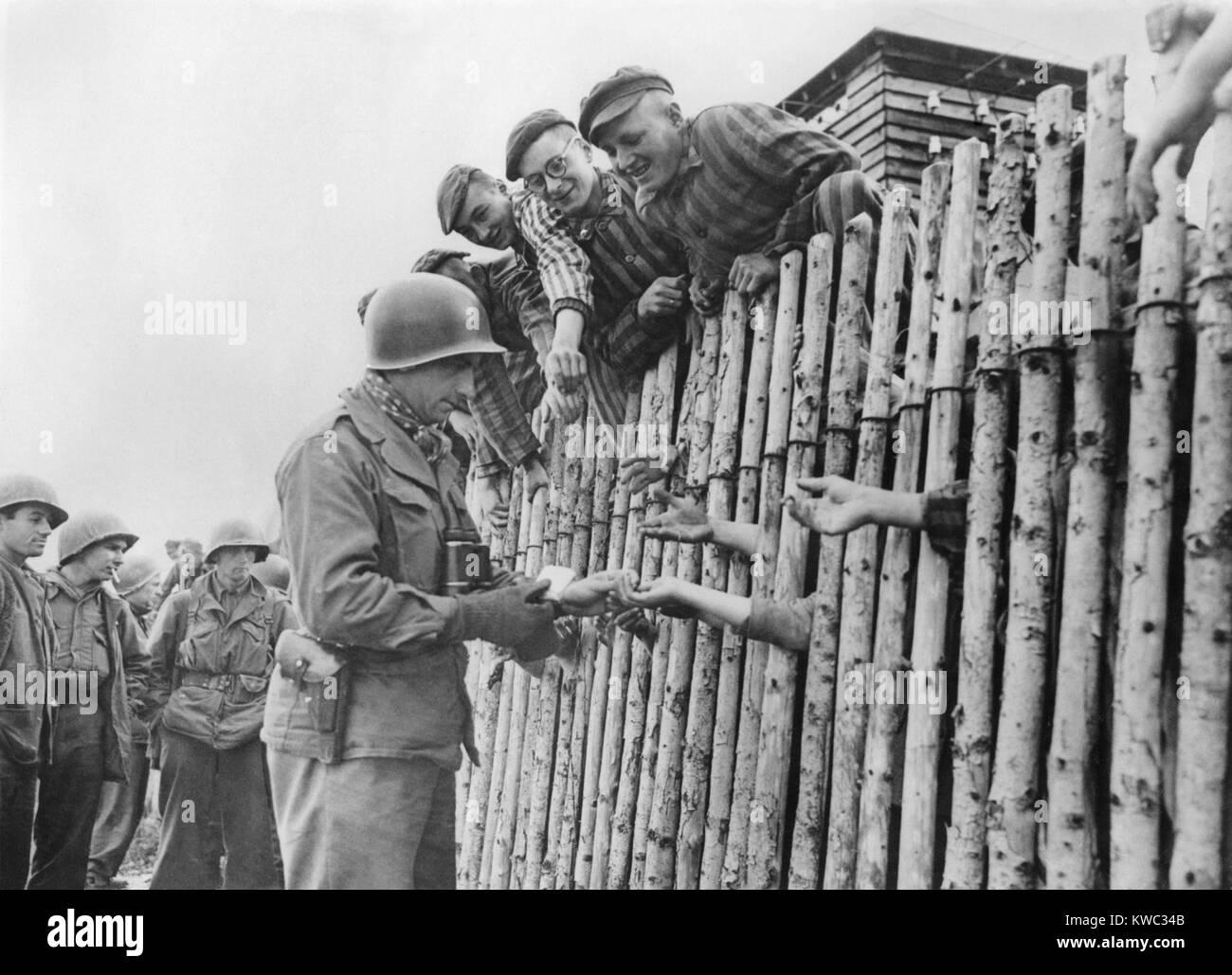 Ig del Séptimo ejército de EE.UU. da su último cigarrillos a liberaron Dachau prisioneros tras una estacada. El Foto de stock