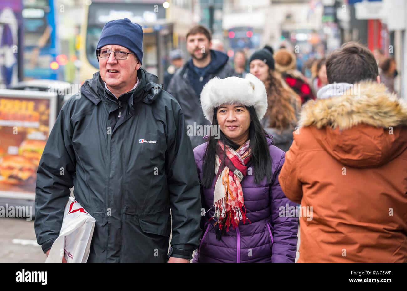 Un par de diferentes orígenes étnicos pasear cogidos de la mano en Inglaterra, Reino Unido. Imagen De Stock