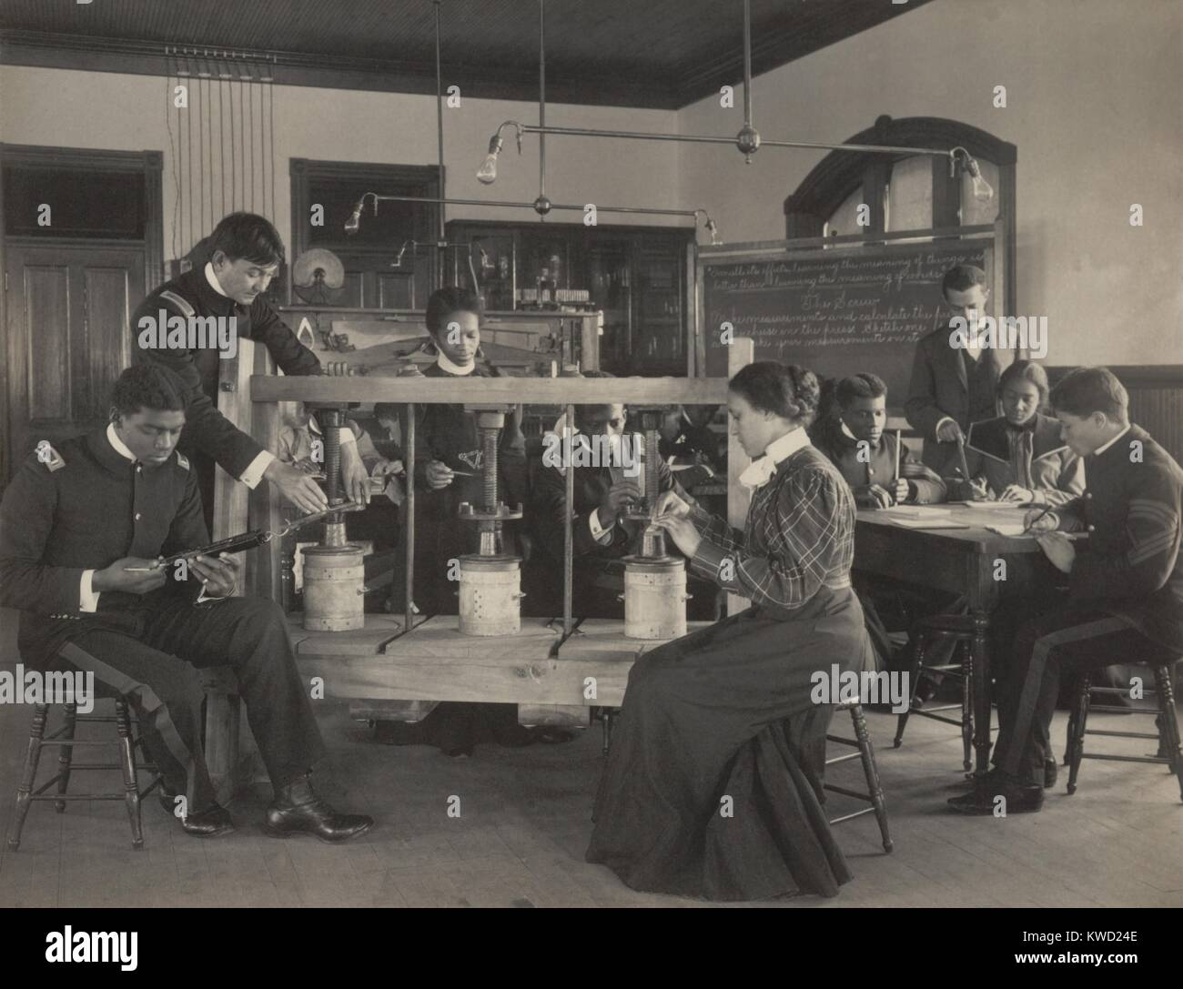 Los estudiantes aprenden a operar una prensa de tornillo de queso en clase de ciencias agrícolas, c. 1899-1900. Foto de stock
