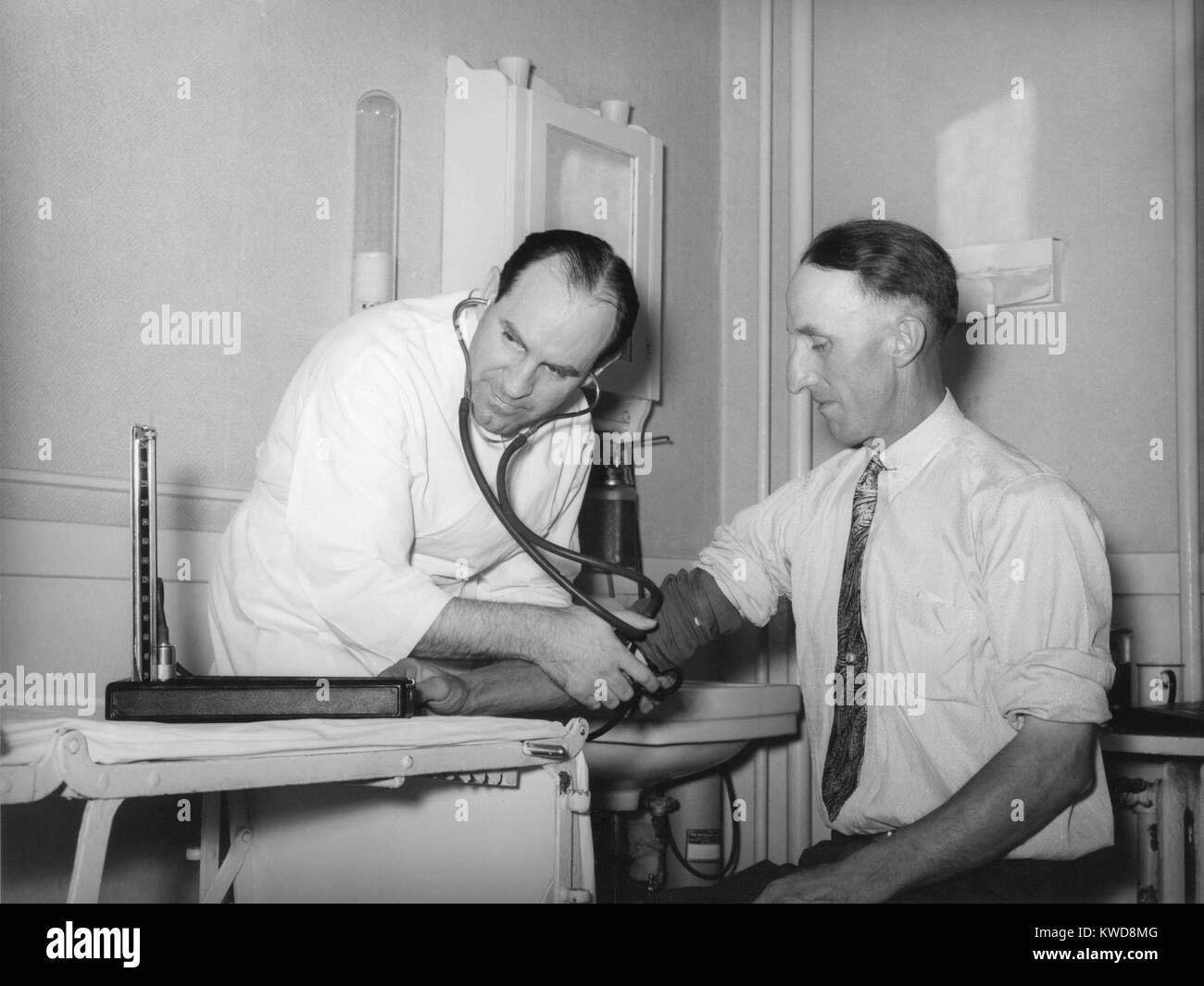 Doctor en una cooperativa médica tomar la presión sanguínea de un paciente en el condado de Box Elder, Utah, 1940. Foto de stock