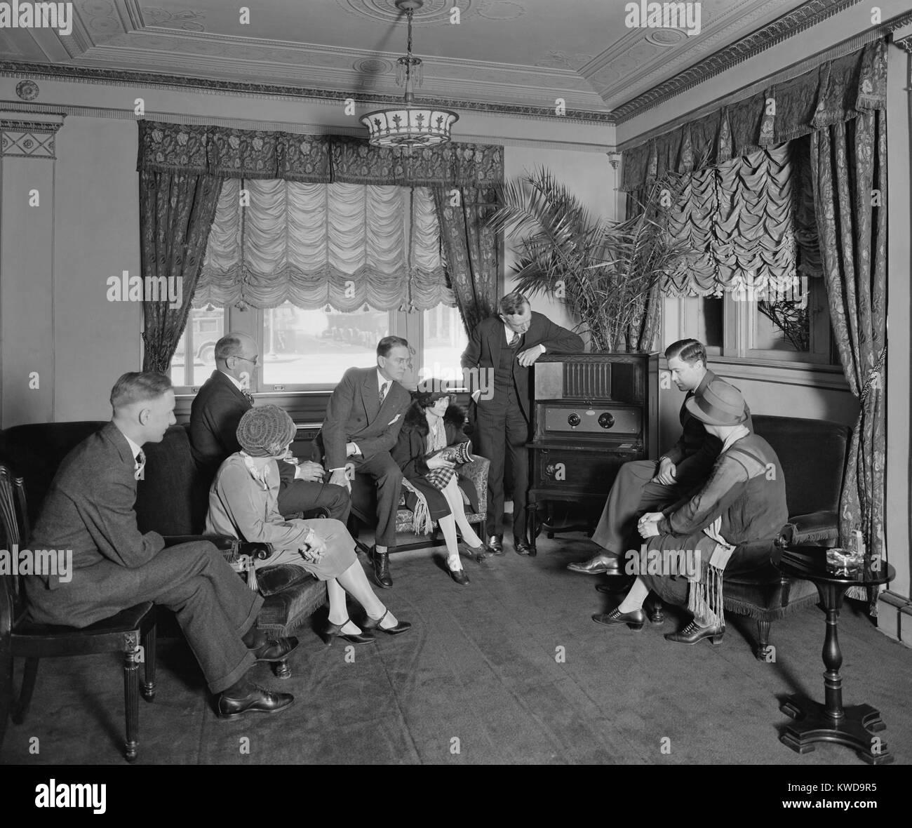 Grupo de hombres y mujeres escuchando una radio en el Hotel Hamilton, Washington, D.C., el Atwater Kent radio incorpora un altavoz cerrado en la parte superior del armario. La foto se asoció con Thomas R. Shipp es trabajo de relaciones públicas para Atwater Kent Radios (BSLOC_2016_10_57) Foto de stock