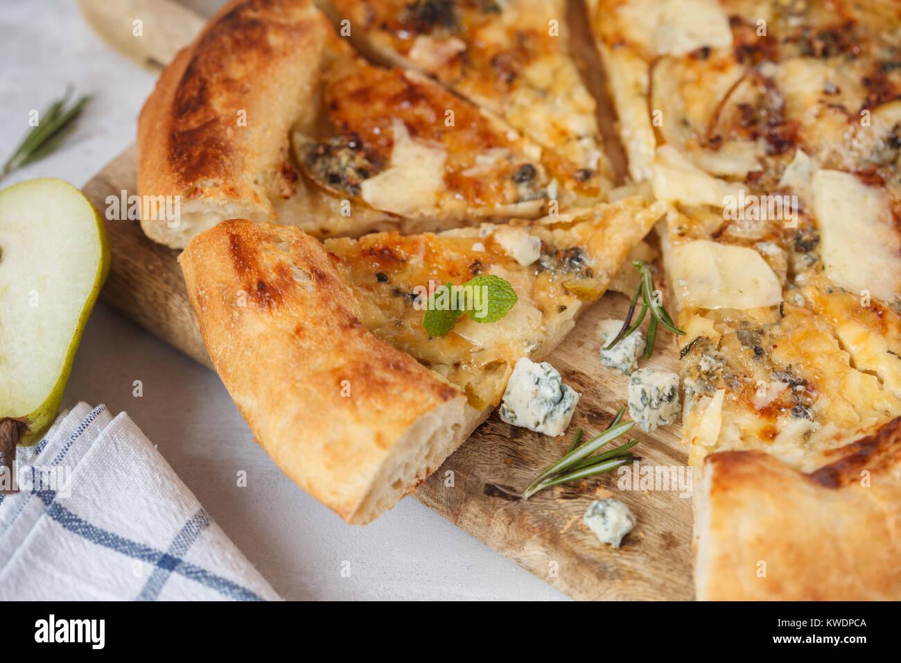 Deliciosa pizza caliente con pera y queso azul sobre la plancha de madera. Concepto de comida saludable vegetariana, Imagen De Stock