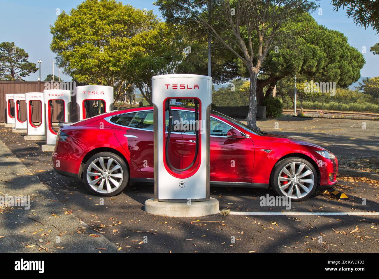 Tesla sedán 'S' conectado a 480 voltios (carga rápida) Estación de supercargador. Imagen De Stock