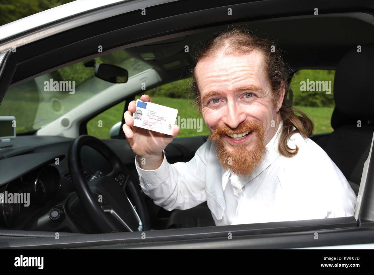 Sonriente conductor sentado en el coche y mostrando la licencia de conductores Imagen De Stock