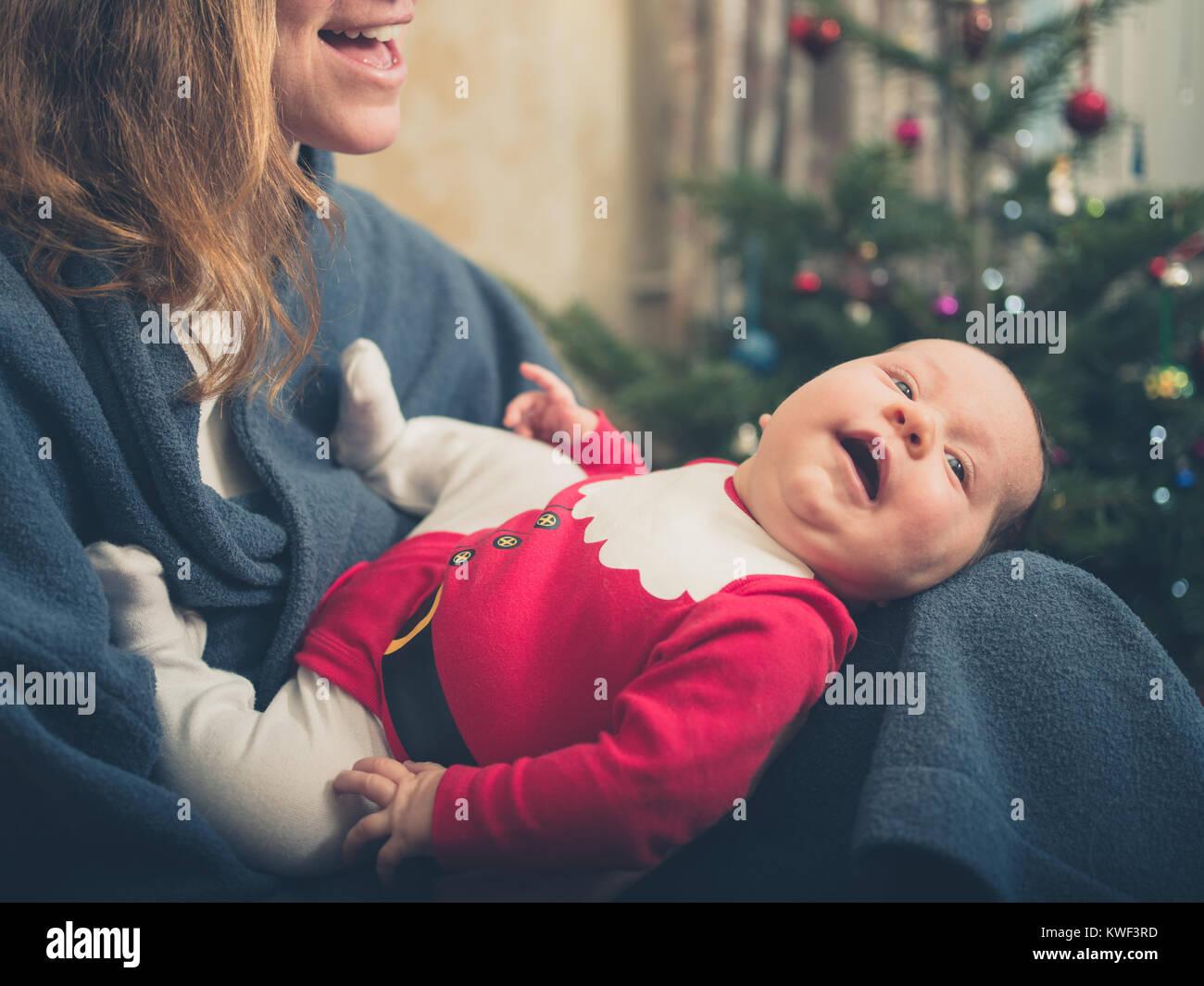 Un bebé feliz vistiendo un traje de santa delante del árbol de Navidad Imagen De Stock