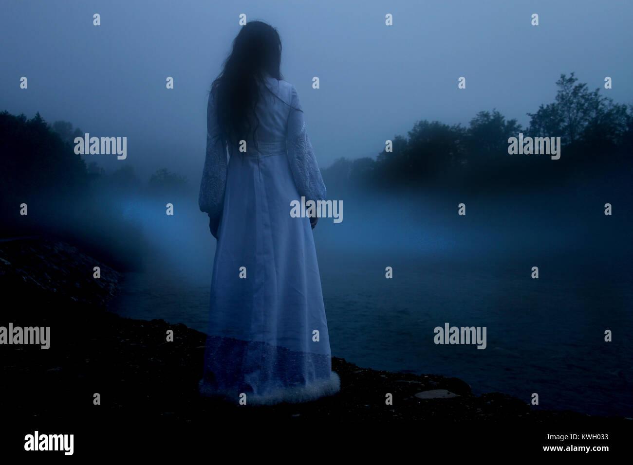 Misteriosa mujer en vestido blanco Foto de stock