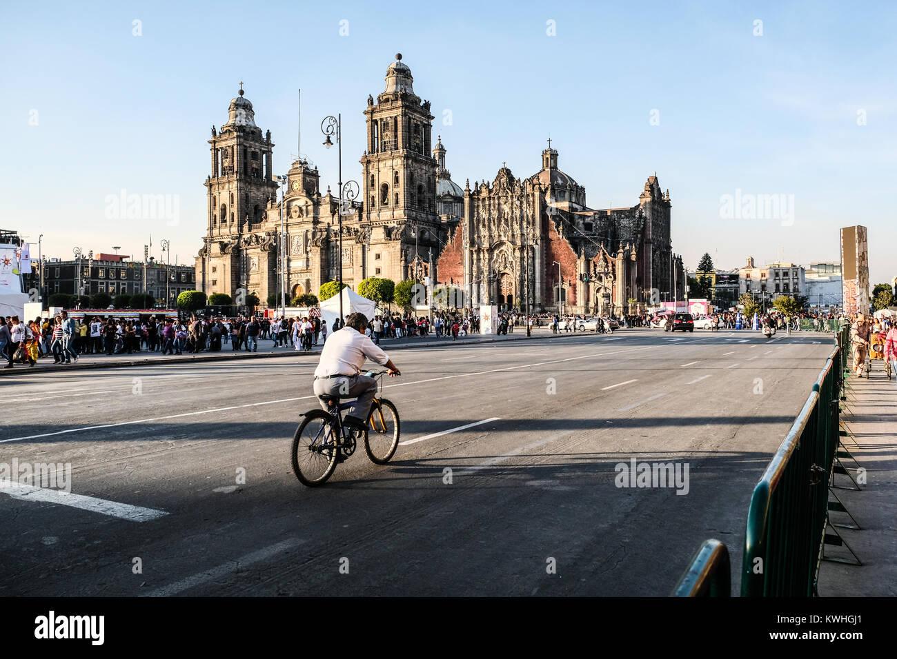 Un ciclista solitario cabalgando sobre calle vacía por la plaza Zócalo de la Ciudad de México Imagen De Stock