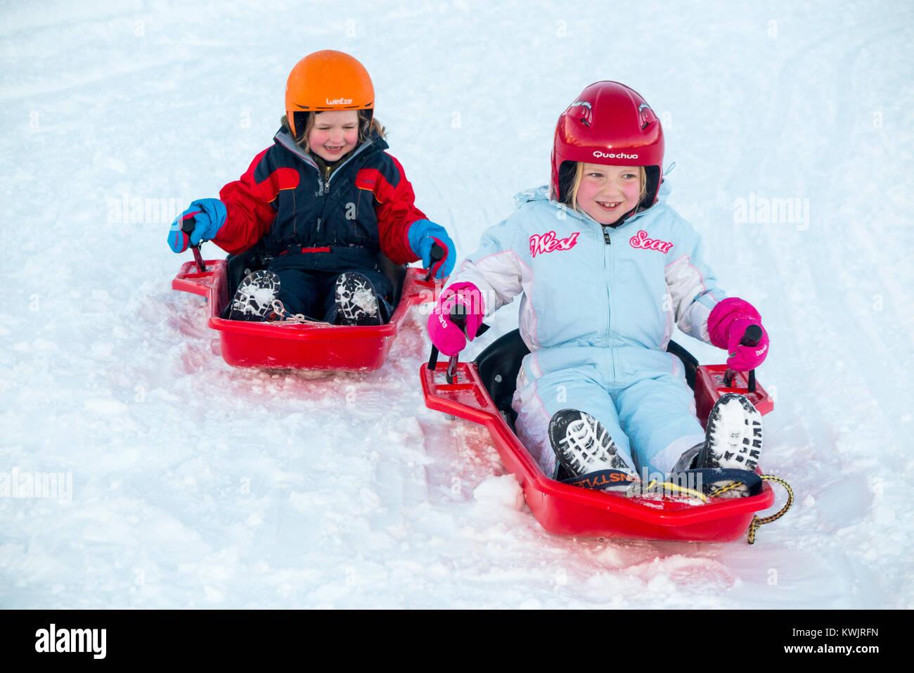 Las niñas, hermanas, de edades comprendidas entre los cinco y siete años de edad, y portando cascos de Imagen De Stock