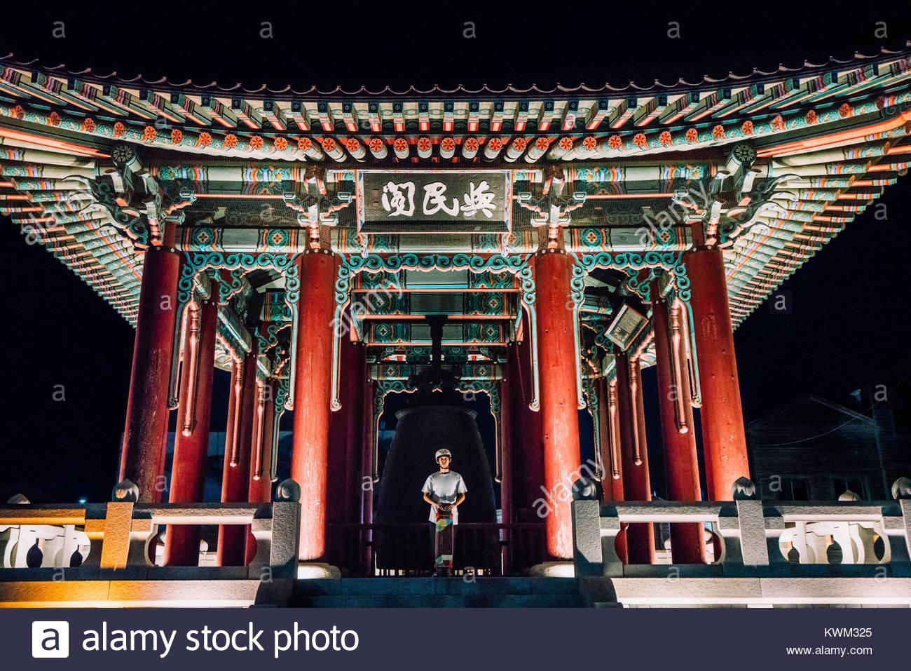 Hombre sujetando el monopatín mientras está de pie en el pabellón en la fortaleza de Hwaseong Imagen De Stock