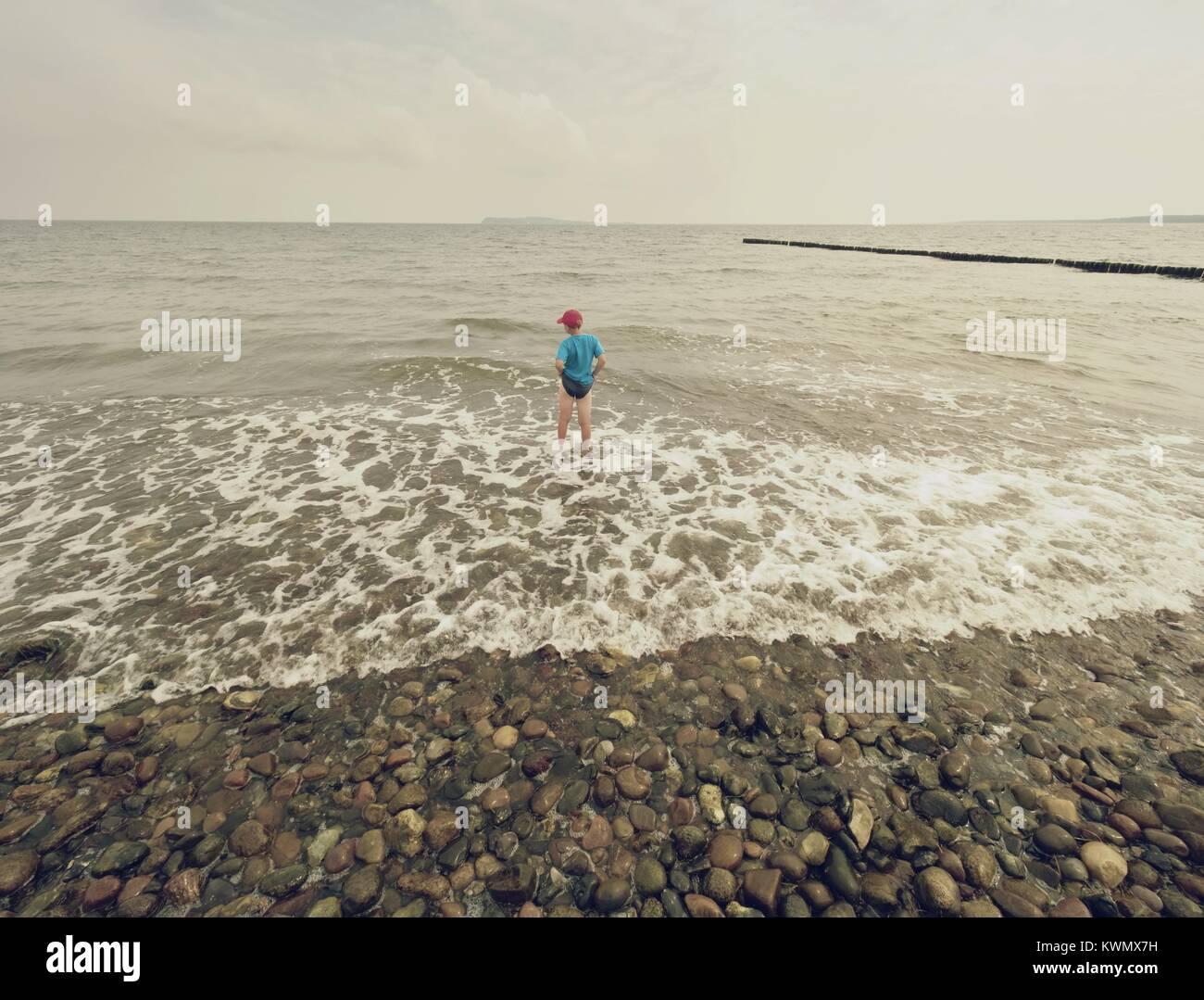 Cabello rubio niño permanecer en frío mar marea. Cabrito en playa de grava de espumosas olas. Día ventoso, nublado Foto de stock