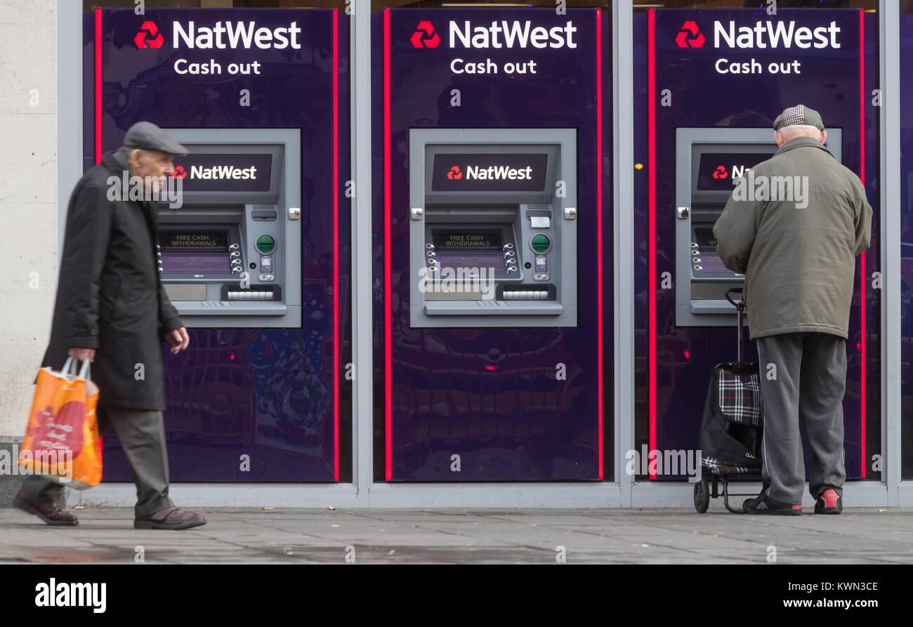 Un pensionista con un cajero automático en una máquina NatWest Bank en Southampton High Street, REINO Imagen De Stock