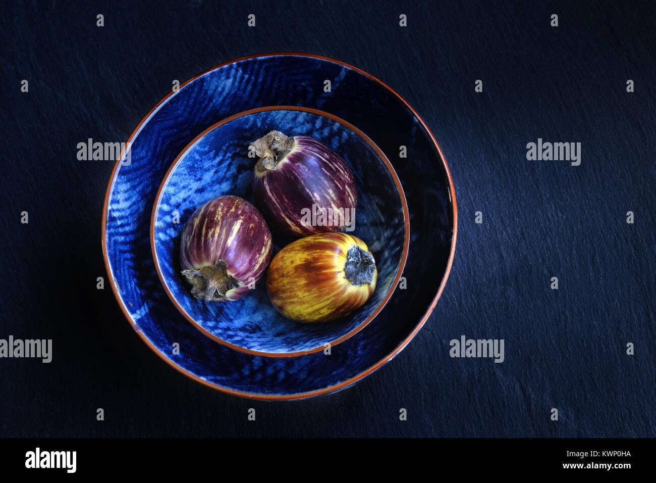 Frescos y saludables berenjenas en un bwols púrpura sobre fondo de piedra oscura. Comida vegetariana, salud Imagen De Stock