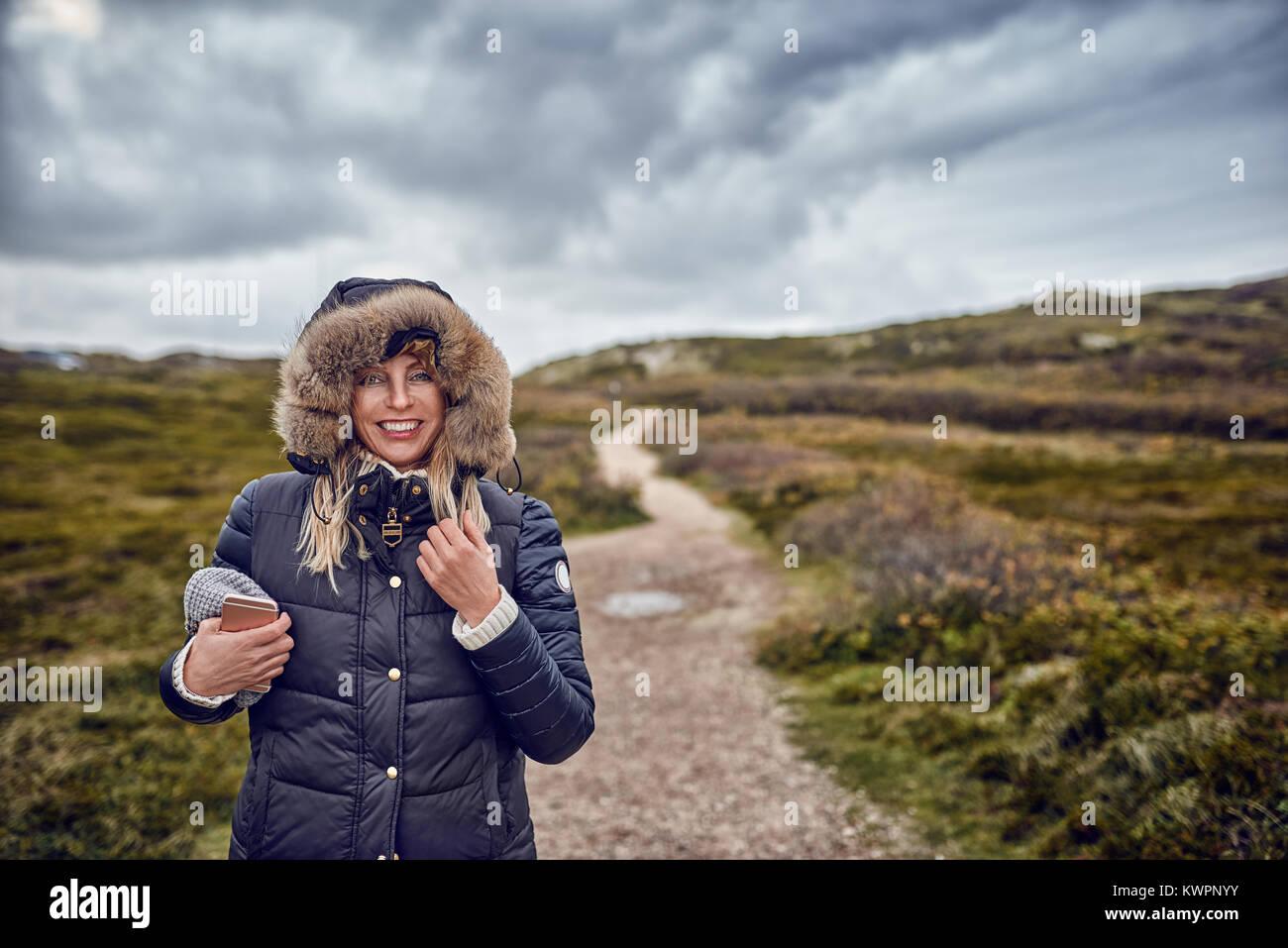 Mujer de mediana edad sorteando un frío día de invierno en la naturaleza caminando por el paisaje en un Imagen De Stock