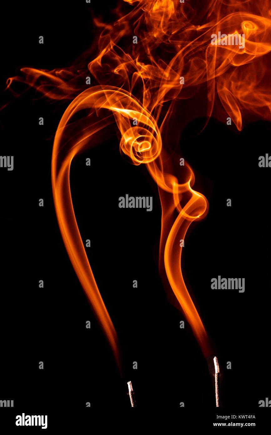 Imagen conceptual de estelas de humo de incienso naranja haciendo formas de interés. Imagen De Stock