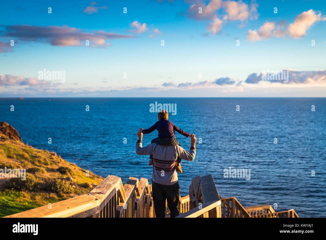 Padre dando su hijo viaje en piggyback Hallett Cove boardwalk mientras disfruta de la puesta de sol, el sur de Australia Imagen De Stock