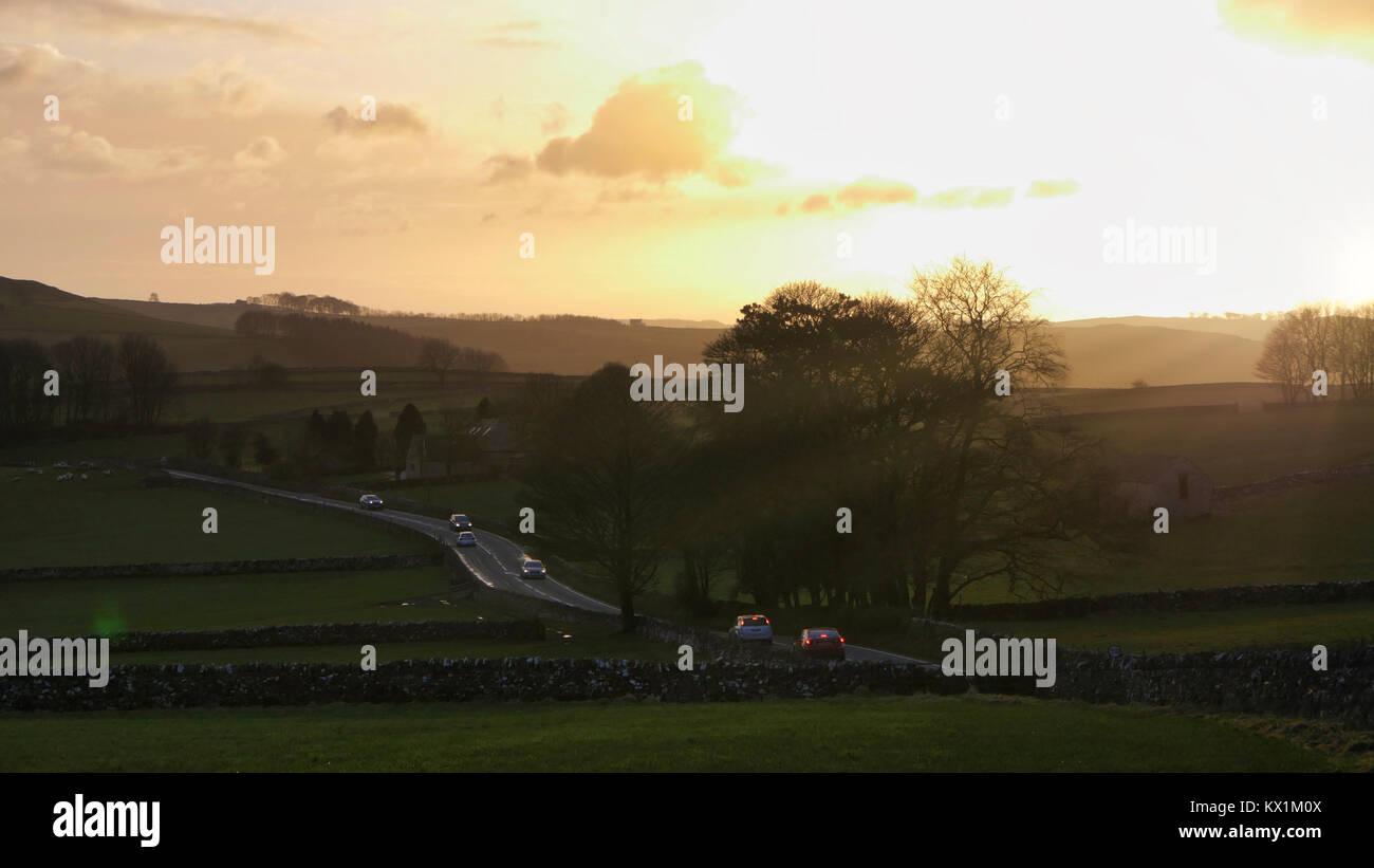 El clima del REINO UNIDO: espectacular puesta de sol a lo largo de la carretera A515 entre Buxton & Ashbourne en el Peak District National Park, Derbyshire Foto de stock