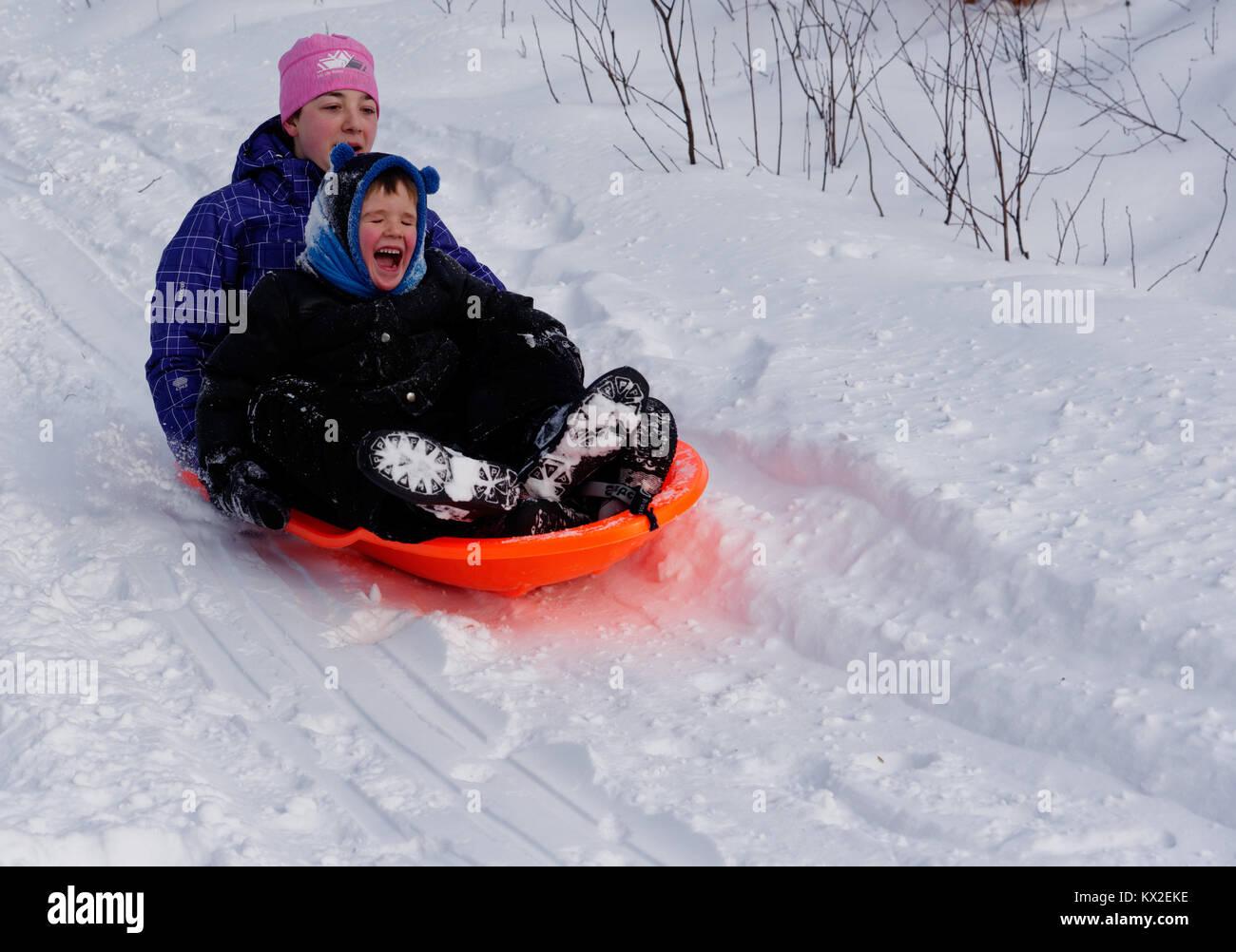 Un adolescente (18 años) en un trineo con un niño pequeño (5 años), buscando nervioso como su Imagen De Stock