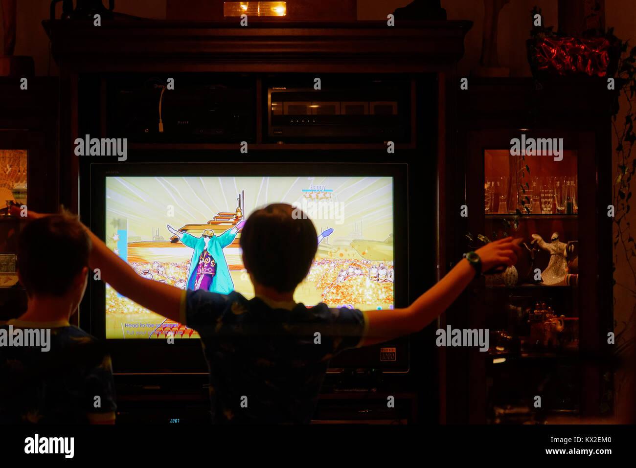 Un joven (9 años) bailando en frente de la TV para la PlayStation 4 Juego Just Dance Foto de stock